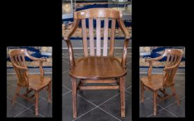 A Golden Oak American Style Captains Chair with a slat back and and with open arms and a contoured