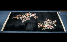 Attractive Wool Rug in black with fringing and decorative coloured floral design.