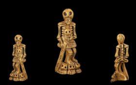 Carved Bone Skeleton figure holding a sw
