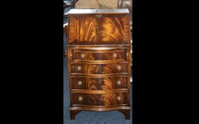 A Small Mahogany Bow Fronted Reproduction Bureau with a fitted interior below four graduated