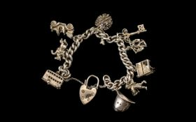 Silver Curb Bracelet Loaded with Eight Good Quality Vintage Silver Charms.
