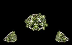 Peridot Flower Cluster Ring, an openwork floral cluster mount set with oval cut peridots of 4.