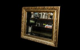 Large Gilt Framed Mirror with Bevelled Edge, The Frame with a Molded Floral Motifs Swept.