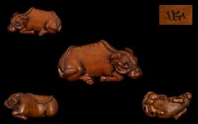 A Japanese Carved Boxwood Netsuke, In The Form of a Water Buffalo,