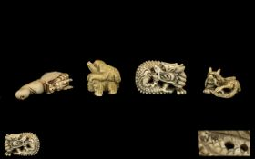 Collection of Four Japanese Netsukes depicting a coiled serpent, a dragon chasing it's tail,