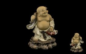 Small Chinese Stoneware Figure of Hotei, on a rocky base, carrying a sack on his back; 8.