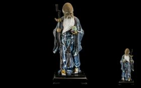 Large Chinese Stoneware Blue Glazed Figure of a Sage holding the peach of immortality and a staff,