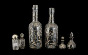 Six Silver Mounted Glass Bottles comprising pair of floral silver overlaid bottle shaped decanters,