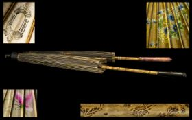 Two Japanese Painted Cloth Parasols with bamboo handles,