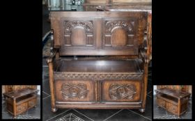 An Oak Folding Top Table Monks Bench with a lift up lidded seat with open arms with two carved