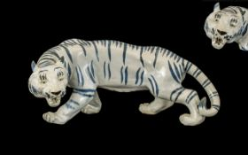 Japanese Figure of a Crouching Lion, picked out to the body with blue stripes; 14 inches long;