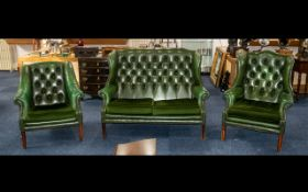 A Three Piece Button Back Green Leather Chesterfield to include a two seater high winged back and