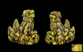 Pair of Antique Chinese Temple Dogs with a brown and yellow speckled glaze, each dog with a paw on a