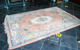 A Chinese Wool Rug 100% Wool. Peach ground with fringed edges, centre circular cream relief.