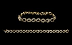 Ladies - Attractive 10ct Gold Baguette Diamond Set Tennis Bracelet of Contemporary Design.