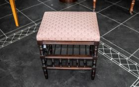 A Modern Cushioned Stop Piano/Dressing Stool with turned gallery form supports and lower shelf.
