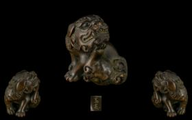 An Oriental Boxwood Netsuke in the form of a foo dog, well carved. Signed to underside.