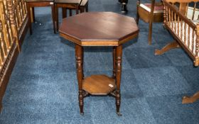 Occasional Table in Mahogany Veneer, raised on four turned legs, with lower shelf, on casters.