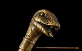 Brass Cobra Head Cane Walking Stick, the snakes tongue protruding from its mouth, ready to strike.