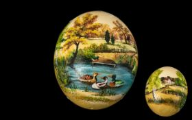 Unusual Painted Ostrich Egg depicting a river landscape with ducks and houses beyond.