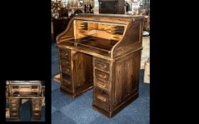 An Early 20th Century Oak Roll Top Pencil Desk of typical form with fitted interior,