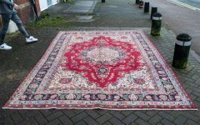 A Genuine Excellent Quality Persian Mashad Carpet/Rug decorated in a floral design on a rich red