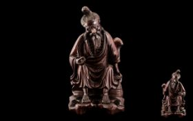 Antique Carved Chinese Cherry Wood Figure of an old man resting by the wayside, holding a rattan