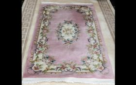 Traditional Rug in shades of pink and cream, with central oval decorative pattern and fringed edges.
