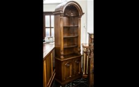 A Modern Yew Wood Bookcase with a shell design pediment above three fixed shelves and storage base.
