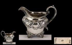 Early Victorian Ornate Embossed Silver Milk Jug of small proportions with swan necked handle gilt