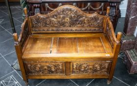 A Carved Stained Pine Monk's Bench, with a lift up seat with carved panels below.