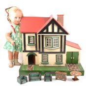 An Amersham Toys wooden dolls house and a composition doll.