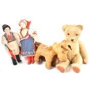 A vintage 1950s straw filled teddy bear, 49cm tall, a straw filled dog, and two character dolls.