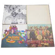 Four The Beatles LP vinyl records.