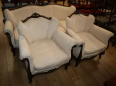 An early 20th century French carved mahogany three piece suite, upholstered in ivory damask