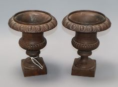 A pair of small cast iron urns height 21cm