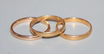 A 22ct gold wedding ring, an 18ct gold wedding ring and a yellow metal wedding ring.