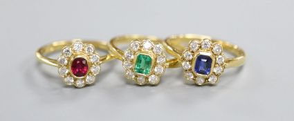 Three modern 18ct gold and gem set cluster rings, to include, emerald, ruby and sapphire, sizes