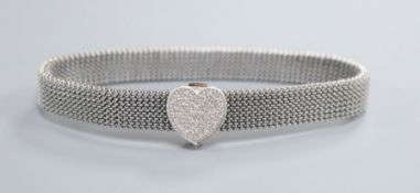 An expanding metal mesh bracelet with a 14k white metal and diamond encrusted heart shaped sliding