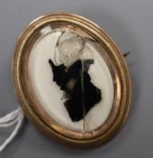An early 19th century yellow metal framed silhouette brooch (damaged glass), 38mm.