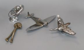 Two chrome car mascots, a skull nut cracker and a model plane