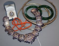 An Indian enamelled white metal necklace, coral bead strand, paste ring, bangles and neck rings.