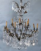 An Italian bronze and cut glass twelve light chandelier, hung with flower and lappet and tear shaped