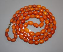 A single strand oval amber bead necklace, gross weight 104 grams, 123cm.