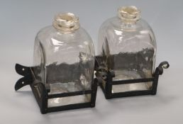 A pair of glass square decanters, on wrought iron stands