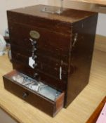 A mahogany six draw dentist's cabinet with tools