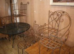 Six wrought iron garden chairs and a circular metal table Diam.122cm