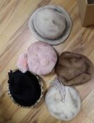 A pink feather hat and four various hats, three being mink
