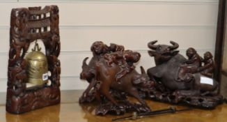 A pair of carved Chinese bulls and riders, a larger similar bull and carved temple bell
