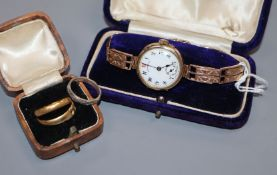 A lady's 9ct gold wrist watch, on a 9ct bracelet and three rings, 22ct, 18ct and stamped 'silver'.